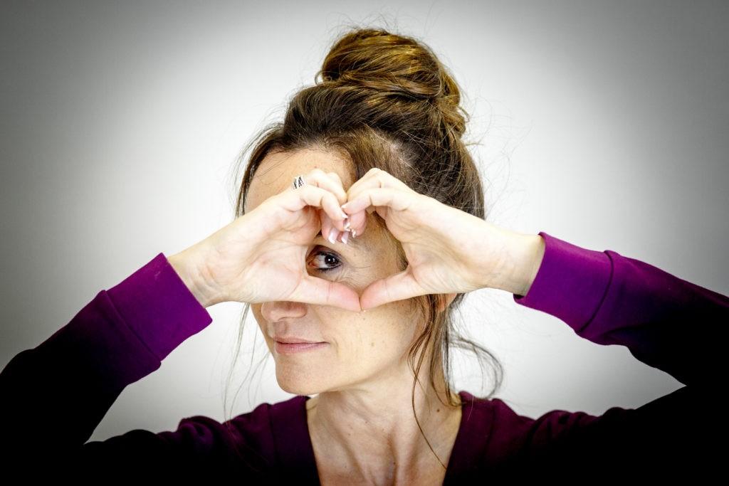 Linda Wnendt formt mit Händen ein Herz und schaut durch